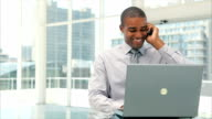 Businessman answering smart phone while using laptop video