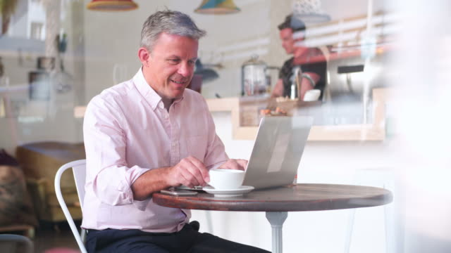 Businessman at a table in a cafe using laptop video