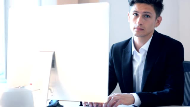 businessman at office working on the computer while pffice routine video
