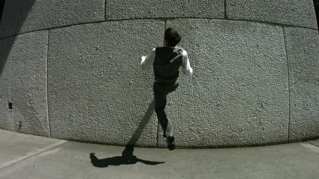 Businessman back flips off wall, slow motion video