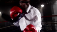 Businessman boxing in ring video
