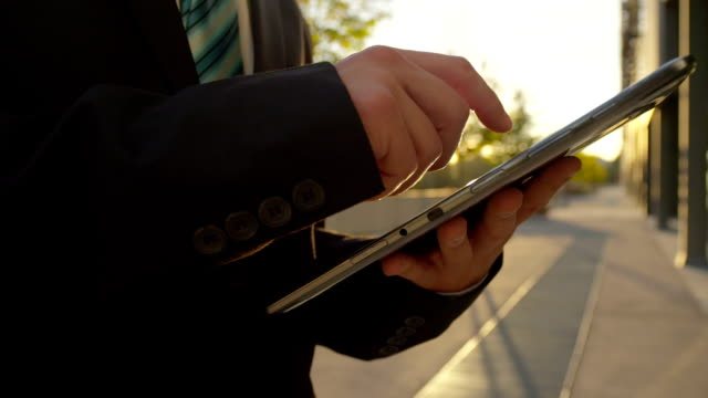 Businessman browsing the news on digital tablet in the morning video