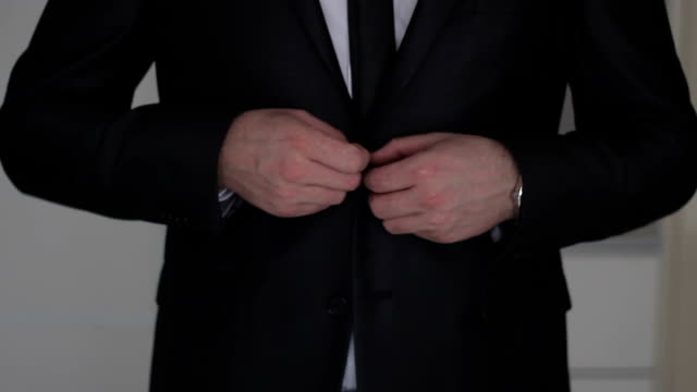Businessman buttoning  to suit video