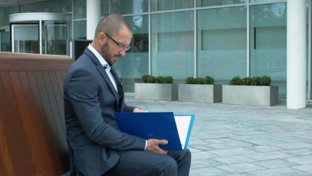 A Businessman Checking Important Documentation In Front Of Office Building video