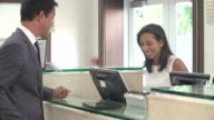 Businessman Checking In At Hotel Reception Front Desk video