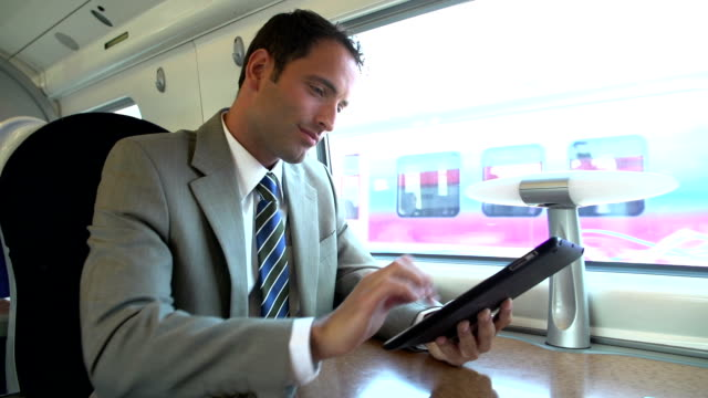 Businessman Commuting On Train Using Digital Tablet video