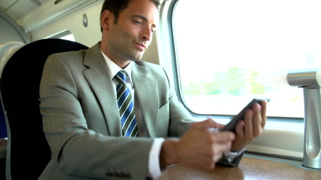 Businessman Commuting To Work On Train Using Mobile Phone video