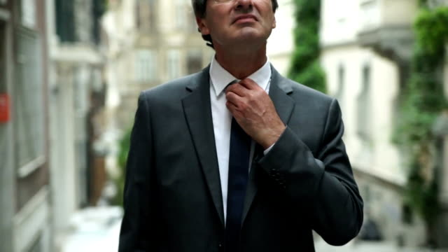 Businessman correcting a tie on street video
