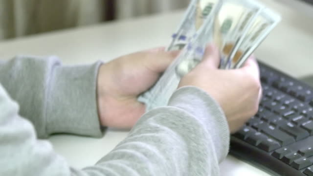 businessman counting dollars in office 4k video