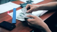 Businessman counting money US dollars on his workplace in office video