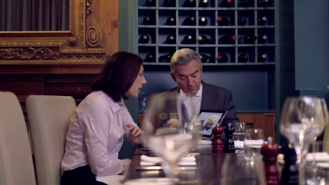 MS PAN Businessman discussing with digital tablet in restaurant video