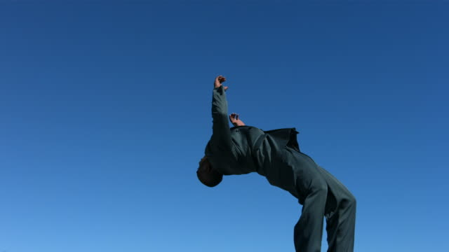 Businessman does a flip, side view, slow motion video