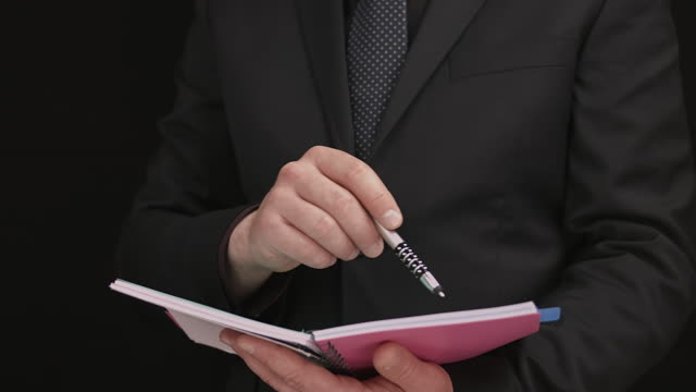 Businessman Dressed In A Black Suit And A Blue Tie Performing An Assessment Of A Contract Data By Holding A Documentation Notebook video