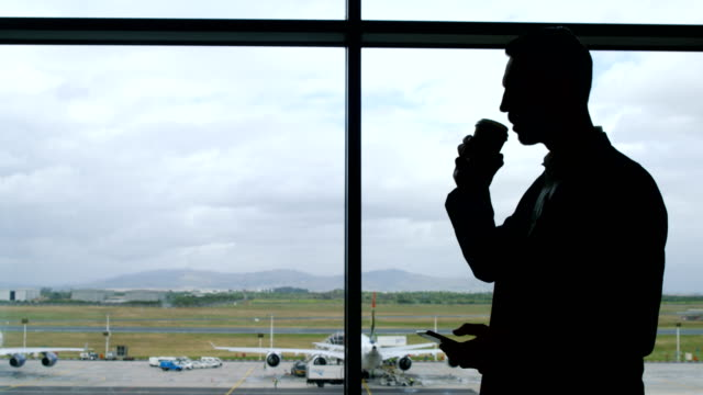Businessman drinking coffee and holding mobile phone at airport video