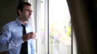 Businessman drinking coffee and looking out of window video