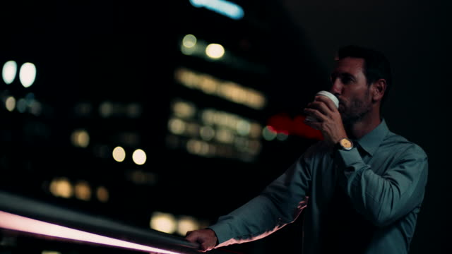 Businessman drinking coffee on balcony and enjoying cityscape video