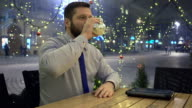 Businessman drinking hot warming drink and has stomach ache, at night in cafe video