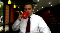 Businessman Drinks Coffee and Reads Newspaper in Cafe video