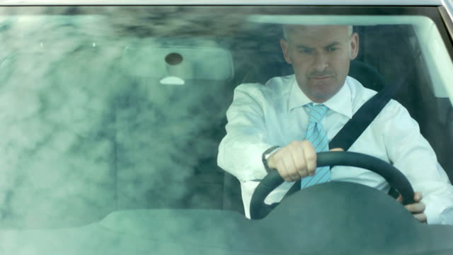 Businessman driving car with sky reflections on windshield video