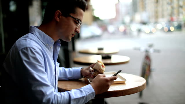 Businessman eating breakfast in sidewalk cafe and using phone video
