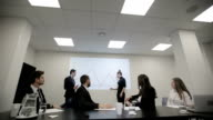 Businessman explaining bar chart to colleagues in a conference room. Slider camera movement video
