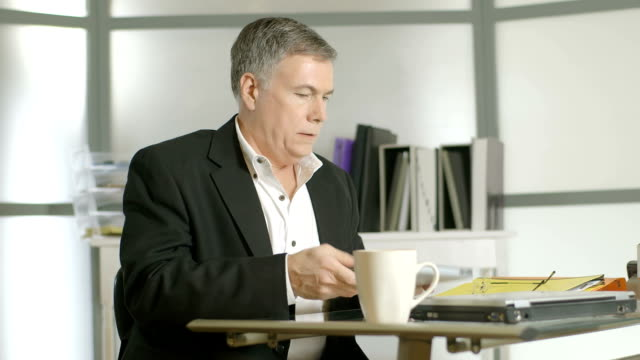 Businessman gets up from desk with back pain video