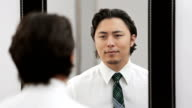 Businessman getting ready in front of the mirror video