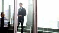 Businessman giving presentation behind glass wall video
