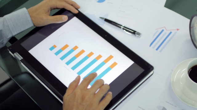 Businessman Hands touching on digital tablet for analyze graph , dolly shot left to right video