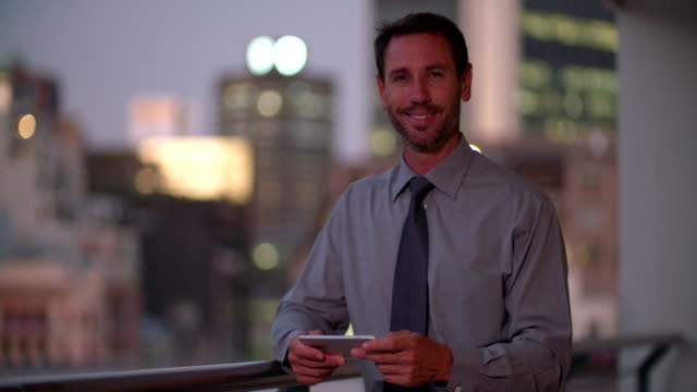 Businessman hodling smartphone in horizontal position on office balcony video