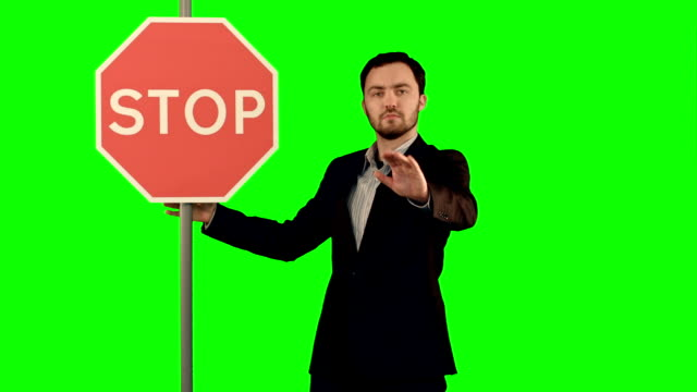 A businessman holding a stop sign on laptop on a Green Screen, Chroma Key video