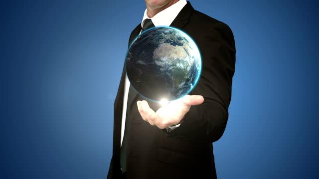 Businessman holding digital generated globe video