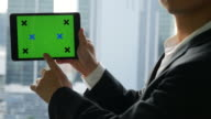 Businessman holding digital tablet with green screen video