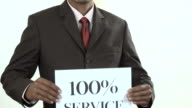 Businessman holding white card with 100% Service sign video