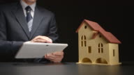 Businessman holds a tablet PC at the hands near a house model on a table video