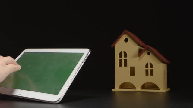 Businessman holds a tablet PC at the hands near a house model on a table (green screen) video
