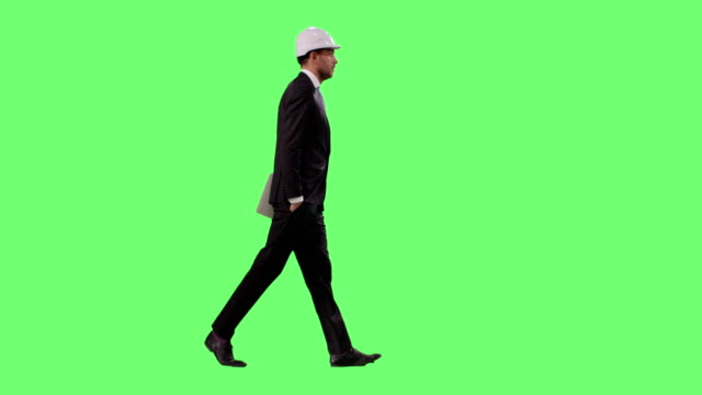 Businessman in a Hard Hat and a Suit is Walking on a Mock-up Green Screen in the Background. video
