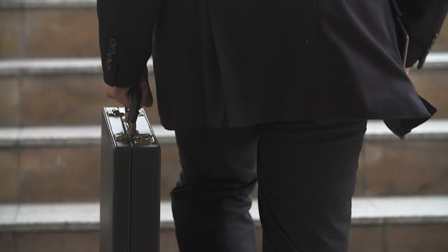 Businessman in a hurry running up stairs, he is late for his business appointment.Focusing on his briefcase. video