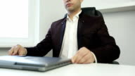 Businessman in a jacket sits on an office chair and working on a laptop. video