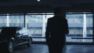 Businessman in a suit is walking towards an executive car in a garage parking lot. video