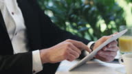 Businessman in a suit uses a tablet at a restaurant table. video