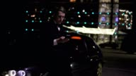 Businessman in a suit using a smartphone next to an luxurious executive car and a big window at the parking. Lights at the background video