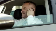 Businessman in car talking on mobile phone video