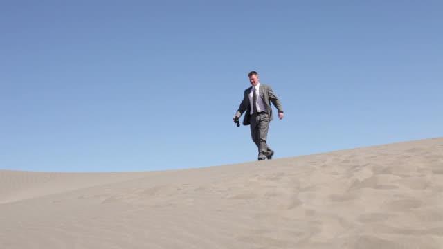 Businessman in desert looking through binoculars video