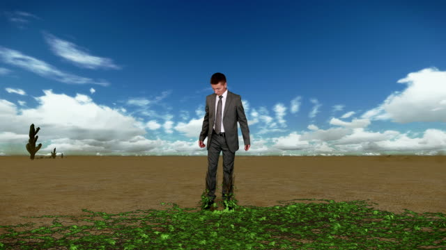 Businessman in Desert with Ivy Growing and Time Lapse Clouds video