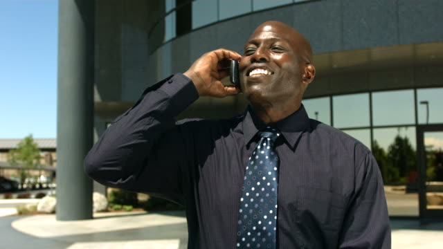 Businessman in front of office building talking on cell phone video