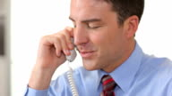 Businessman in office talking on telephone video
