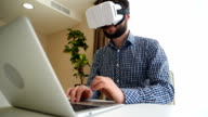 businessman in virtual reality glasses on his laptop video
