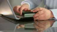 Businessman inserting credit card number, online banking service video