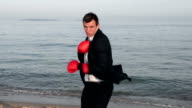 Businessman is boxing at the seaside video